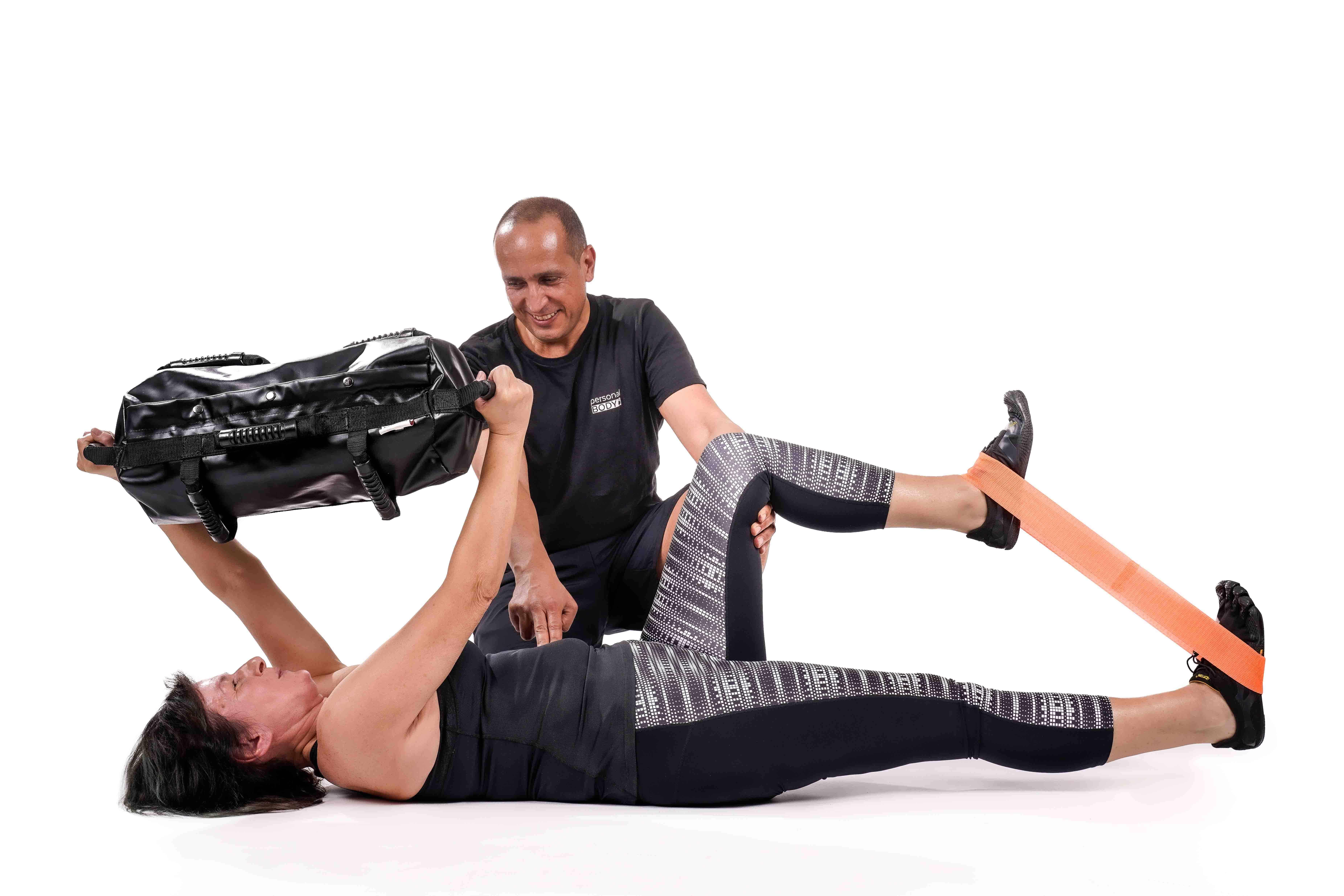 Personal Trainer mit Ultimate Sandbag Dead Bug mit Miniband